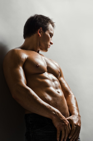 athletic type: the very muscular handsome sexy guy on   grey wall  background