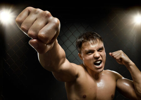 horizontal  photo  muscular young  guy street-fighter, cuff  fist close up on camera and yell , hard light Stock Photo - 26813822