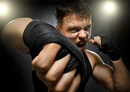 horizontal  photo  muscular young  guy street-fighter, cuff  fist close up on camera and yell , hard light Stock Photo - 26813824