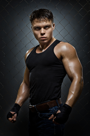 fiercely: vertical photo  muscular young  guy street-fighter,  aggression look, hard light