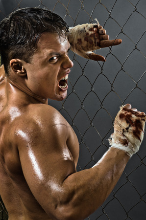 fiercely: vertical photo  muscular young  guy street-fighter,  aggression awesome yell , hard light
