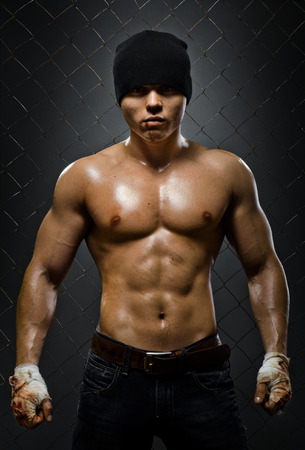 hard look: vertical photo  muscular young  guy street-fighter,  aggression look, hard light