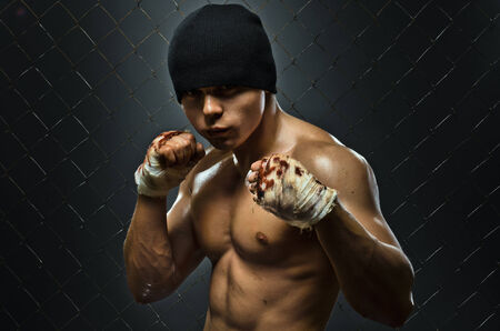 fiercely: horizontal photo  muscular young  guy street-fighter,  aggression look, hard light