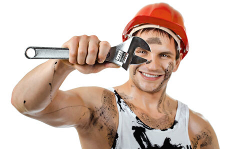 happy worker man, dirty in  safety helmet  with big wrench  in hands, turn on and smile, on white background, isolated photo