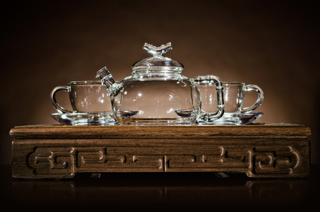 trivet: horizontal  photo  of the glass teapot with  cup on  wooden trivet, on dark background Stock Photo