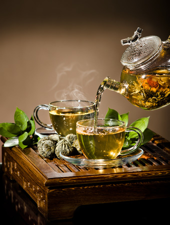 strew: vertical photo, of the glass teapot flow green tea in cup on brown background,  tea ceremony Stock Photo