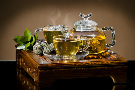 strew: horizontal photo, of the glass teapot flow green tea in cup on brown background,  tea ceremony