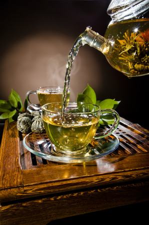 vertica: vertical photo, of the glass teapot flow green tea in cup on brown background,  tea ceremony Stock Photo