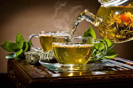 brown cup tea: horizontal photo, of the glass teapot flow green tea in cup on brown background,  tea ceremony