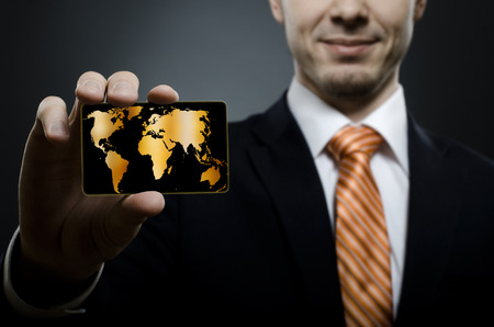 businessman in black costume and orange necktie reach out on camera and show credit card or visiting card, close up photo