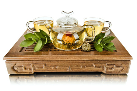 tea set: still life of the glass teapot flow green tea in cup on wooden trivet, white background, isolated,  tea ceremony