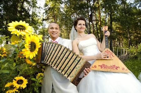 merrymaking: fiancee blow the balalaika,  bridegroom play on accordion, wedding  humour photo
