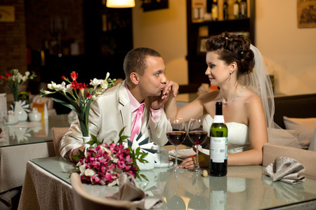 newly married couple sit at table in restaurant,  romance wedding dinner, kiss photo