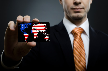 financier: businessman in black costume and orange necktie reach out on camera and show credit card or visiting card, close up
