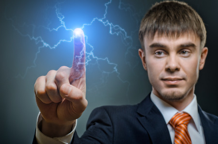 handsome businessman finger point touch electric strike  lightning, on dark blue background Stock Photo