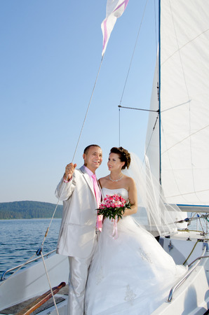 vertical photo  happy newly married couple stand on  white yacht, outdoor, wedding trip photo