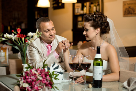 newly married couple sit at table in restaurant,  romance wedding dinner photo