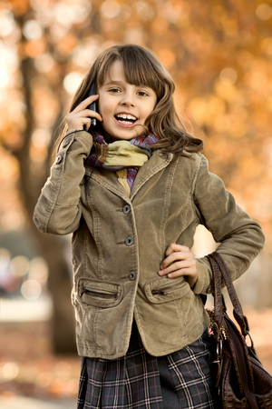 telephony: vertical photo,  stylish beautiful little girl hold  mobile phone and gladness talk