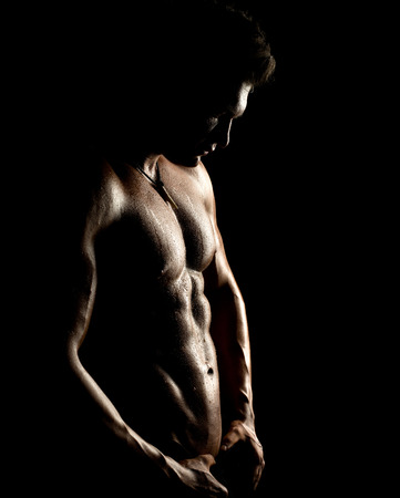 the very muscular handsome sexy guy on black background, naked  torso photo