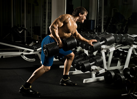 musculation: very power athletic guy ,  execute  traction with  dumbbells, exercise on broadest muscle of back, in sport hall