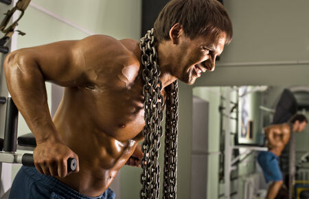 musculation: very power athletic guy ,  execute exercise on parallel bars, workout  in sport hall Stock Photo