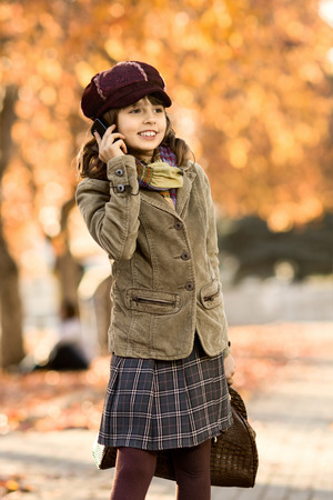 gladness: stylish beautiful little girl hold  mobile phone and gladness talk Stock Photo