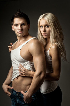pareja apasionada: muscular guapo chico sexy con una mujer bonita, sobre fondo azul oscuro Foto de archivo