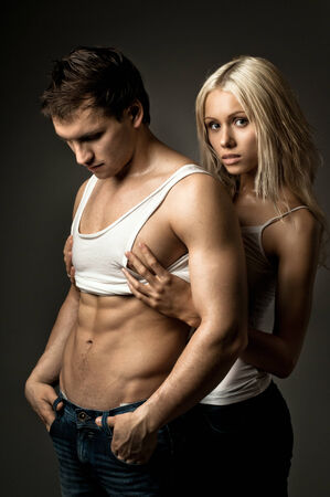 muscular handsome sexy guy with pretty woman, on dark blue  background photo