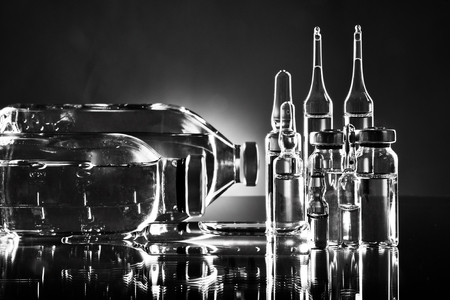 demijohn: group object of  liquid medicinal agent in  limpid glassware, black-and-white horizontal photo Stock Photo