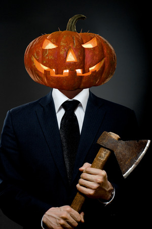 horrific: Man in black costume with pumpkin head  with axe, Halloween concept