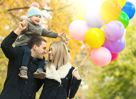 merrymaking: happy family with little child and air-balloons, outing in autumn park Stock Photo