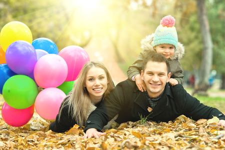 lively: happy family with little child and air-balloons, outing in autumn park Stock Photo