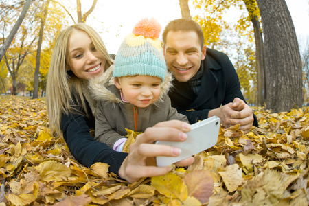 family outing: happy family with little child take Selfie on telephone, outing in autumn park