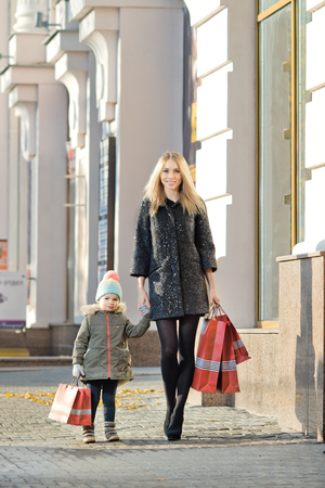 street kid: happy woman and little child with red shopping bag, walking on street Stock Photo