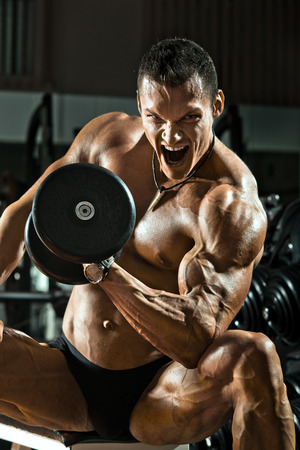 hardy: very power athletic guy ,  execute exercise with  dumbbells, on bkack background Stock Photo
