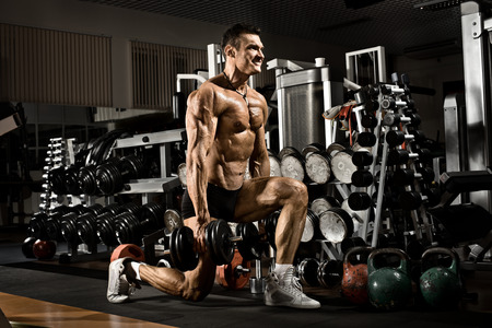 musculation: very power athletic guy ,  execute exercise with  dumbbells, in gym