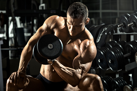 sport training: very power athletic guy bodybuilder ,  execute exercise with  dumbbells, in dark gym