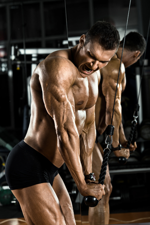 musculation: very power athletic guy bodybuilder,  execute exercise with gym apparatus, on triceps