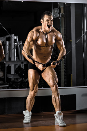 pectoral muscle: very power athletic guy bodybuilder,  execute exercise with gym crossover apparatus, on pectoral muscle