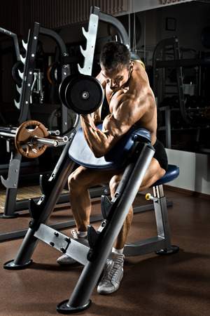 very power athletic guy bodybuilder,  execute exercise with  dumbbells, on Scotts bench photo