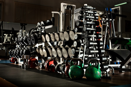 many black dumbbells in gym room, horizontal photo