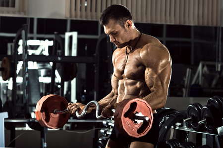 vigorously: very power athletic guy bodybuilder ,  execute exercise with  with  weight, in dark gym Stock Photo