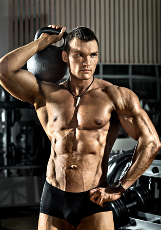 musculation: portrait very brawny athletic guy - bodybuilder,   with  weight, in gym Stock Photo