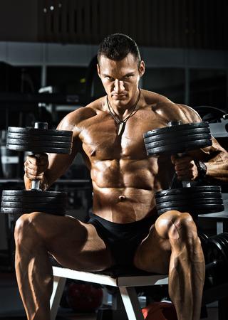 muskeltraining: sehr Macht athletische Kerl Bodybuilder, sitzen mit Hanteln, in dunklen Turnhalle Lizenzfreie Bilder