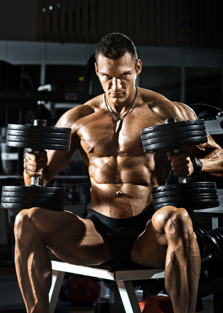 musculation: very power athletic guy bodybuilder , sit with  dumbbells, in dark gym Stock Photo