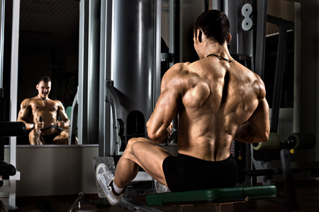 muscle strain: very power athletic guy bodybuilder,  execute exercise with gym apparatus, on broadest muscle of back Stock Photo