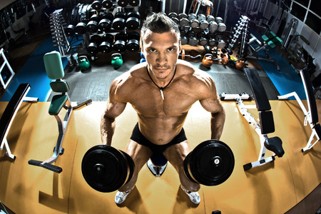 musculation: muscle athletic guy bodybuilder ,  with dumbbells , in gym