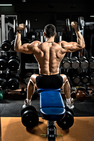 brawny: very brawny guy bodybuilder,  execute exercise with  dumbbells, on deltoid muscle shoulder Stock Photo