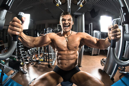 brawny: very brawny guy bodybuilder ,  execute exercise  on gym apparatus Butterfly Machine, in gym