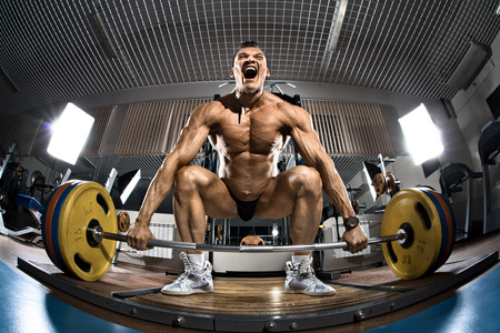 brawny: very brawny guy bodybuilder ,  execute exercise deadlift with weight, in gym
